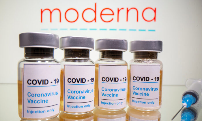 "Vials with a sticker reading ""COVID-19/Coronavirus vaccine/Injection only"" and a syringe are seen in front of a displayed Moderna logo in this illustration taken October 31, 2020. (Reuters/Dado Ruvic/Illustration/File Photo)"