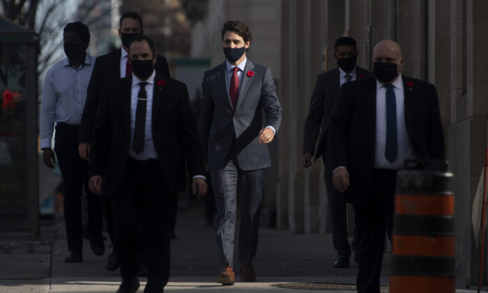 Prime Minister Justin Trudeau and his security detail walk past a construction worker as they make their way to a news conference in Ottawa,  on Nov. 10, 2020. (Adrian Wyld/The Canadian Press)