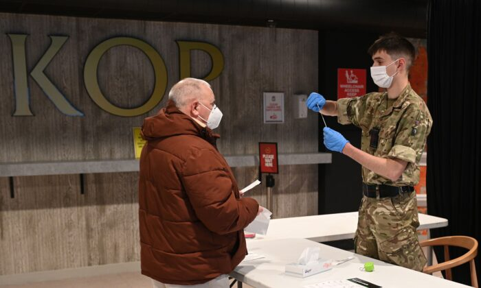 A British Army soldier hands a member of the public a swab and provides information on its use inside Anfield Stadium, in Liverpool, on Nov. 10, 2020 (Oli Scarff/AFP via Getty Images)