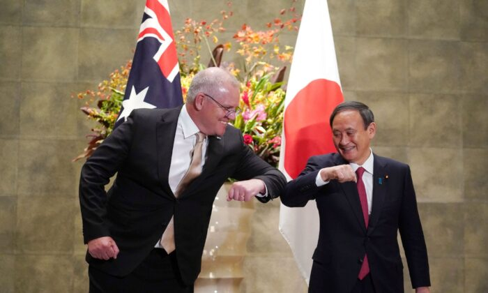 Australia's Prime Minister Scott Morrison (L) is greeted by Japan's Prime Minister Yoshihide Suga (R) prior to an official welcoming ceremony at Suga's official residence in Tokyo on November 17, 2020. (Eugene Hoshiko / POOL / AFP)