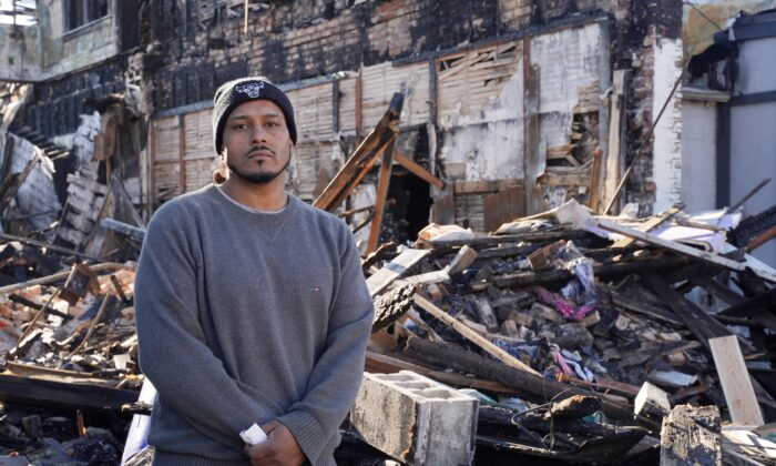 José Martínez stands in front of a burned-down apartment building in the Uptown area of Kenosha, Wis., on Nov. 12, 2020. (Cara Ding/The Epoch Times)