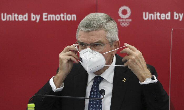 ThomasBach, International Olympic Committee president,puts his mask on after a press conference in Tokyo, Japan, on Nov. 16, 2020. (DuXiaoyi/Pool)