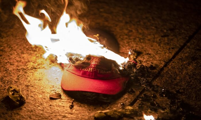 "Members of an Antifa group burn a Trump Train hat following the ""Million MAGA March"" in Washington on Nov. 14, 2020. (Samuel Corum/Getty Images)"
