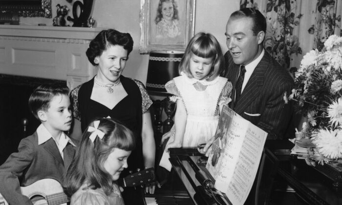 American television show host Ralph Edwards and his family sing songs around a piano, circa 1955. (Hulton Archive/Getty Images)
