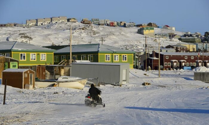 A snowmobiler makes their way along a road in Iqaluit, Nunavut, on Wednesday, March 6, 2019. Nunavut is shutting down for two weeks starting today to try to get cases of COVID-19 under control. (THE CANADIAN PRESS/Sean Kilpatrick)