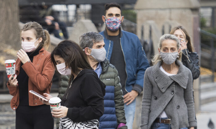 People wear face masks as they walk along a street in Montreal on Nov. 7, 2020, as the COVID-19 pandemic picks up steam. (The Canadian Press/Graham Hughes)