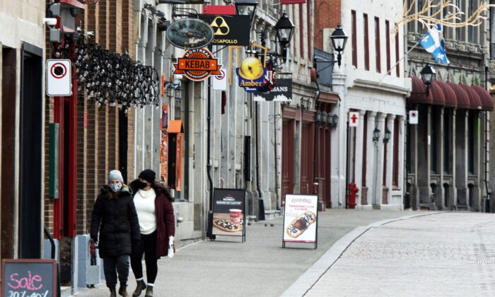 People walk along a deserted street in Old Montreal on Nov. 18, 2020. (The Canadian Press/Ryan Remiorz)