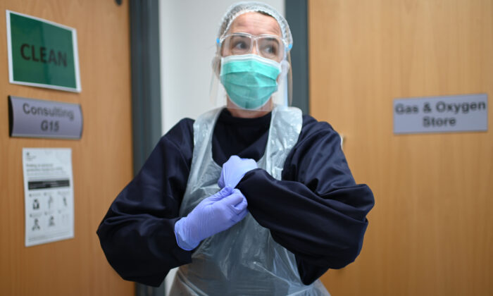 Dr. Nathalie Dukes dons personal protective equipment (PPE) at Freshney Green Primary Care Centre in Grimsby, England, on June 9, 2020. (Daniel Leal-Olivas/AFP via Getty Images)