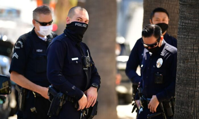 "Los Angeles Police Department officers wear facial covering while monitoring an ""Open California"" rally in downtown Los Angeles, on April 22, 2020. (Frederic J. Brown/AFP via Getty Images)"