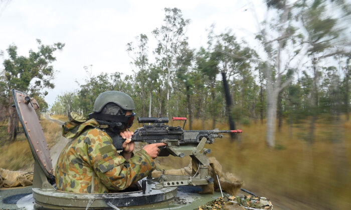 An Australian soldier operates a machine gun on the top turret of a Bushmater amoured vehical as part of exercise Talisman Sabre  in Rockhampton, Australia on July 9, 2015. (Ian Hitchcock/Getty Images)