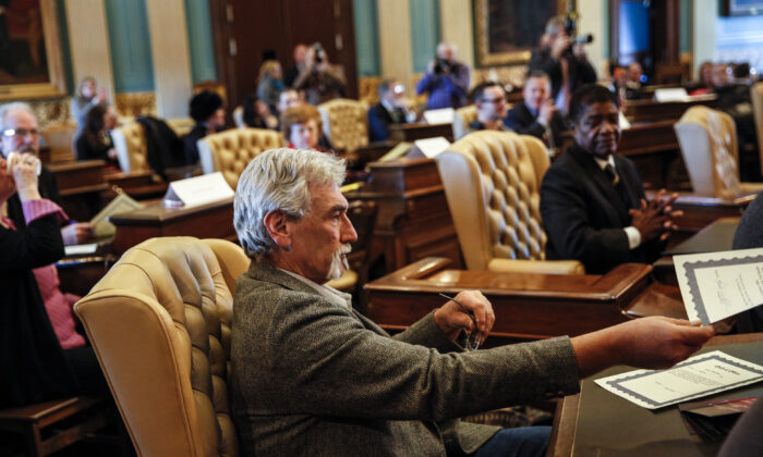 Robert Weitt, a Michigan representative to the electoral college, hands in his signed vote for President-elect Donald Trump at the Michigan State Capitol in Lansing, Mich., on Dec. 19, 2016. (Sarah Rice/Getty Images)