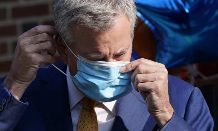 New York Mayor Bill de Blasio puts on a mask during a news conference outside the Mosaic Pre-K Center on the first day of school in New York on Sept. 21, 2020. (Mark Lennihan /AP Photo)