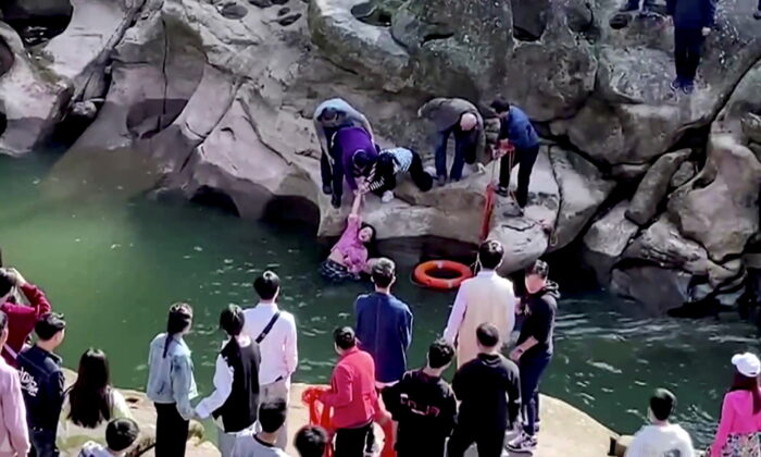 In this screengrab taken from video, Stephen Ellison, British consul-general in Chongqing, rescues a drowning student at a scenic spot in Chongqing, China, on Nov. 14, 2020. (Jiang Lang via British consulate in Chongqing/via Reuters TV)