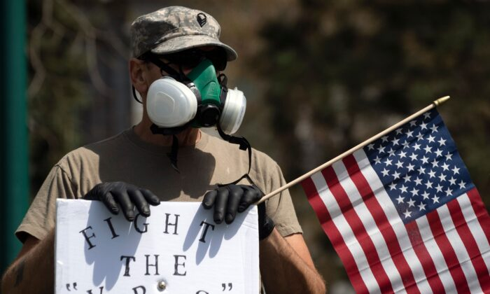 A demonstrator wearing a respirator mask and holding a US flag gathers with others to protest restrictive orders imposed during the COVID-19 pandemic, during a rally in Denver, Colo., on April 19, 2020. (Jason Connolly/AFP via Getty Images)