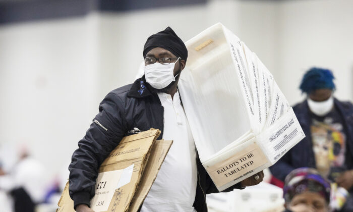 A worker with the Detroit Department of Elections carries empty boxes used to organize absentee ballots after nearing the end of the absentee ballot count at the Central Counting Board in the TCF Center in Detroit, Mich., on Nov. 4, 2020. (Elaine Cromie/Getty Images)