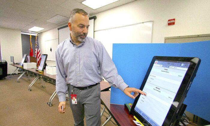 A Dominion Voting Systems employee demonstrates a voting machine in Atlanta, Georgia, on Nov. 13, 2019. (AP Photo/John Bazemore, File)