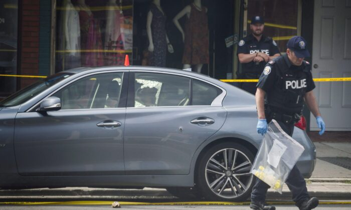 Police investigate a car with a bullet hole at the scene of a shooting in east Toronto, on July 23, 2018. (The Canadian Press/Christopher Katsarov)