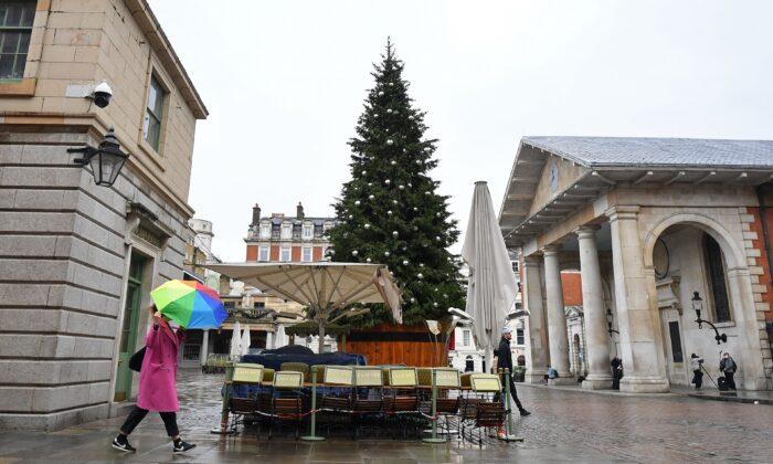 People walk in the rain past a solitary Christmas Tree in a near-deserted Covent Garden in central London, on Nov. 19, 2020,  (Justin Tallis/AFP via Getty Images)