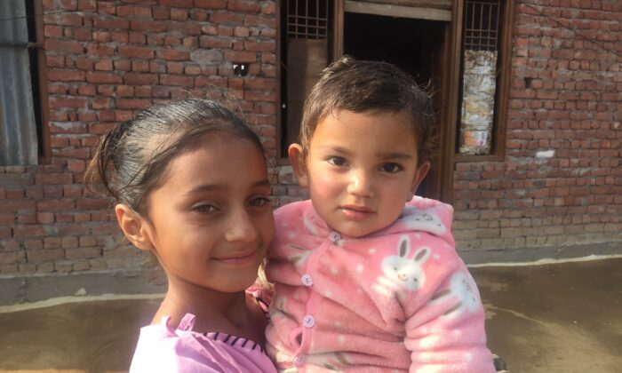 Prachi, 8, and Preetika Chaudhary, 18 months, outside their home on the India–Pakistan disputed border in village Kalal of Rajouri district in Jammu, India, on Nov. 16, 2020. (Venus Upadhayaya/Epoch Times)