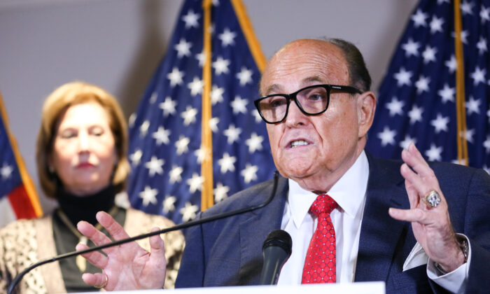 Trump lawyer and former New York City Mayor Rudy Giuliani speaks to media as Trump campaign lawyer Sidney Powell looks on during a press conference at the Republican National Committee headquarters in Washington on Nov. 19, 2020. (Charlotte Cuthbertson/The Epoch Times)