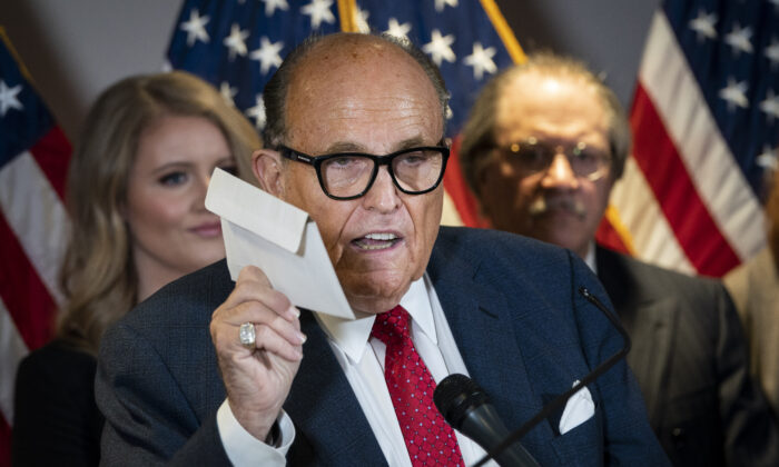 Rudy Giuliani holds up a mail-in ballot as he speaks to the press about various lawsuits related to the 2020 election,  inside the Republican National Committee headquarters in Washington, on Nov. 19, 2020. (Drew Angerer/Getty Images)