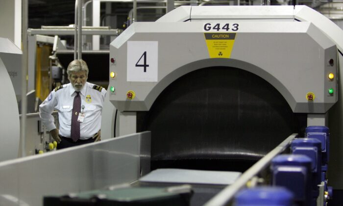 A transportation security administration worker monitors bags as they enter an explosive detection system at the Oakland International Airport in Oakland, Calif., in a file photo. (Justin Sullivan/Getty Images)