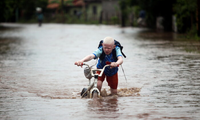 A child pushes his bicycle through a flooded road after the passing of Storm Iota, in Marcovia, Honduras, on Nov. 18, 2020. (Jorge Cabrera/Reuters)