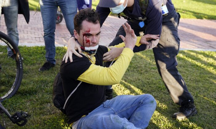 A supporter of President Donald Trump is bleeding after being assaulted by two reported Antifa members, during a pro-Trump rally in Washington on Nov. 14, 2020. (Jacquelyn Martin/AP Photo)