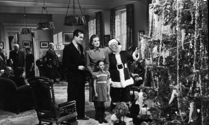 "(L–R) Actors John Payne, Maureen O'Hara, Edmund Gwenn (as Santa Claus), and young Natalie Wood stand before a Christmas tree in a still from director George Seaton's 1947 film, ""Miracle on 34th Street."" (Hulton Archive/Getty Images)"