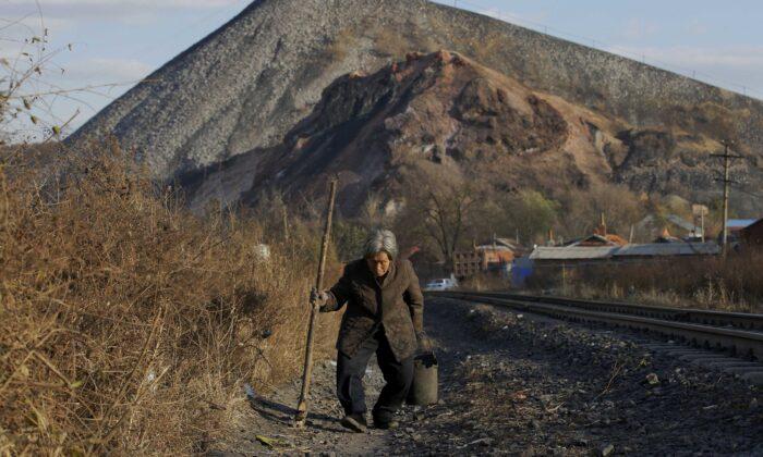 An elderly villager walks along a railway line on the outskirts of Jixi, in Heilongjiang province, China, on Oct. 24, 2015. (Jason Lee/Reuters)