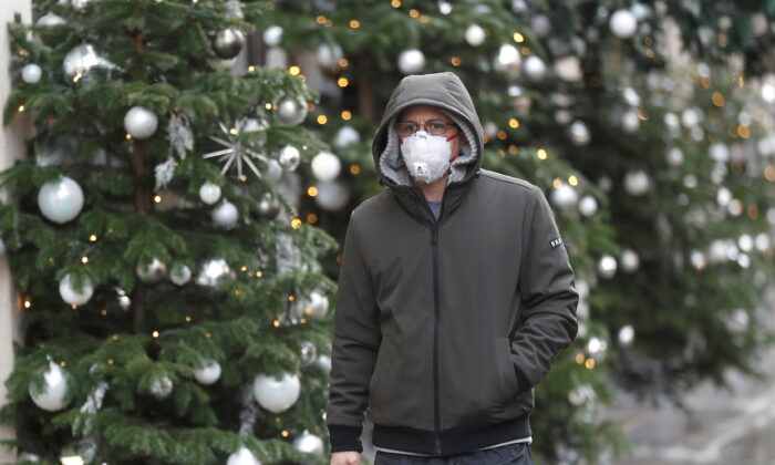 A man walks past Christmas decorations outside a store amid the CCP virus outbreak in London on Nov.19, 2020. (Reuters/Peter Nicholls)