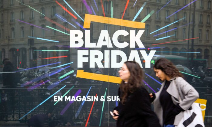 """Pedestrians walk past a store window with a sign announcing the so-called """"Black Friday"""" sales in Paris on Nov. 23, 2018. (Stringer/AFP via Getty Images)"""