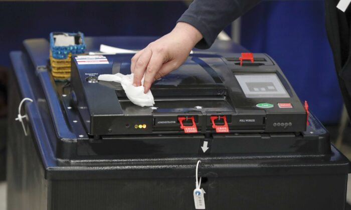 A voting machine is cleaned during the Illinois Democratic primary in Chicago on March 17, 2020. (Kamil Krzaczynski/AFP via Getty Images)