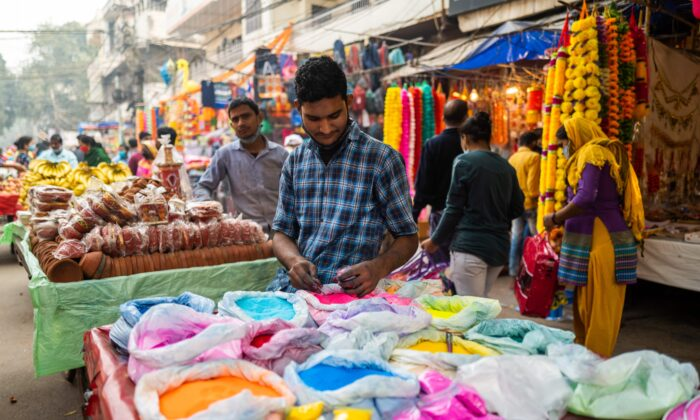 A vendor packs color powder used to make decorations for Diwali, the Hindu Festival of Lights, as he waits for customers in a market area in New Delhi on Nov. 14, 2020. (Jewel Samad/AFP via Getty Images)