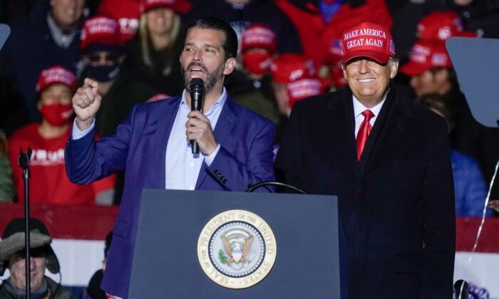 Then-President Donald Trump watches as Donald Trump Jr. speaks at a campaign event at the Kenosha Regional Airport in Kenosha, Wis., on Nov. 2, 2020. (Morry Gash/File/AP)