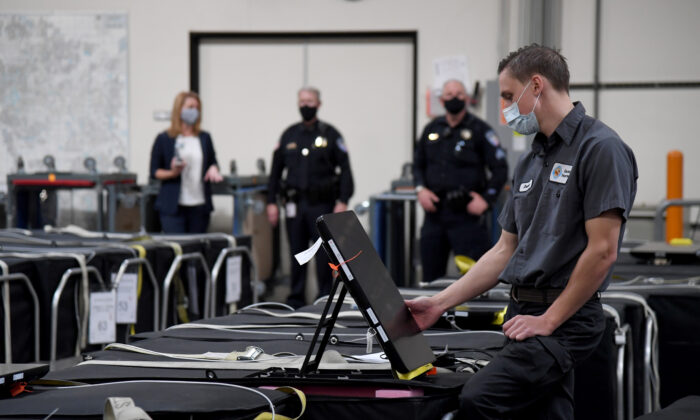 A Clark County election worker checks a voting machine among others that are boxed up at the Clark County Election Department in Las Vegas, on Nov. 6. (Ethan Miller/Getty Images)