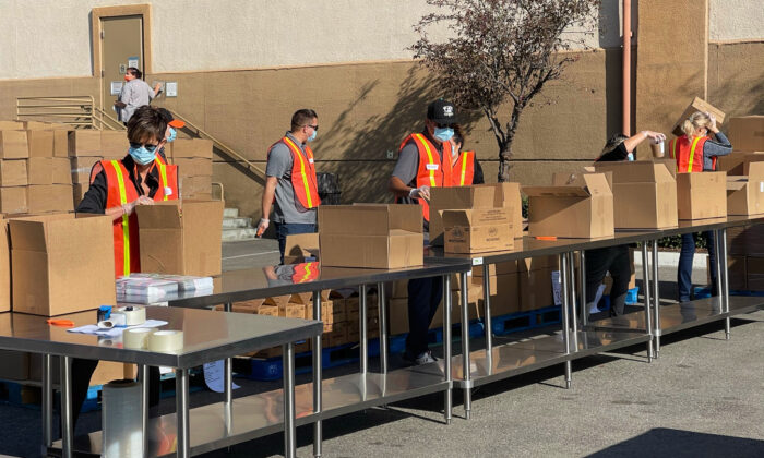 Volunteers prepare Thankgiving meal boxes for the needy at Second Harvest Food Bank headquarters in Irvine, Calif., on Nov. 19, 2020. (Drew Van Voorhis/The Epoch Times)