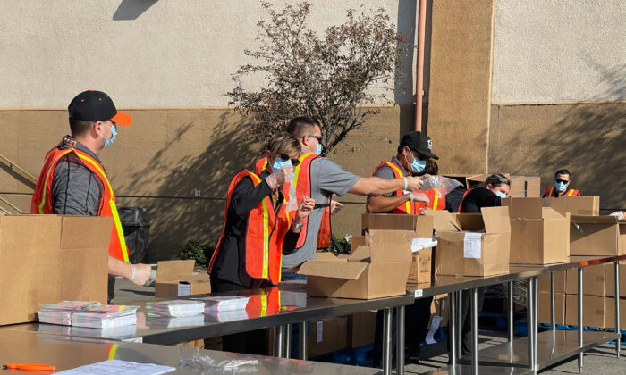 Volunteers with masks stuff boxes for Thanksgiving at the Second Harvest Food Bank in Irvine, Calif., on Nov. 19, 2020. (Drew Van Voorhis/The Epoch Times)