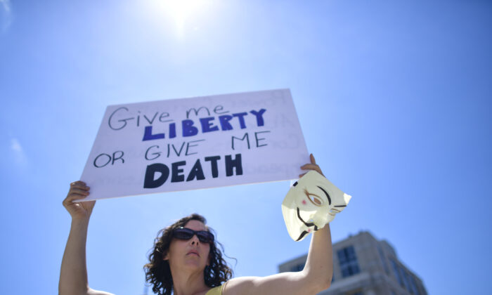 """A woman holds a placard stating """"Give me LIBERTY OR GIVE ME DEATH"""" while joining demonstrators at a rally outside the Pennsylvania Capitol Building to protest the continued closure of businesses due to the coronavirus pandemic  in Harrisburg, Pennsylvania, on May 15, 2020.  (Mark Makela/Getty Images)"""