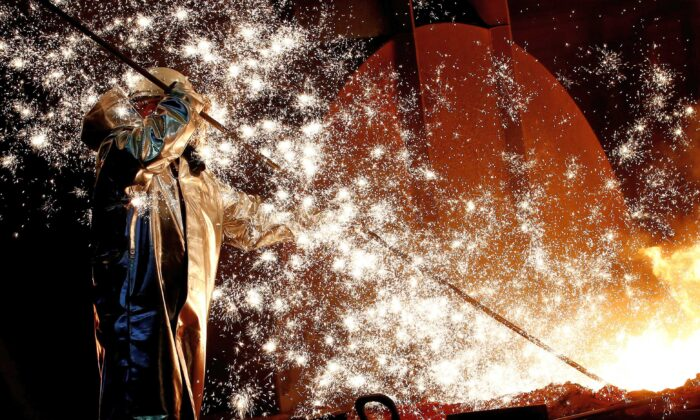 In this file photo a steel worker of Germany's industrial conglomerate ThyssenKrupp AG stands a mid of emitting sparks of raw iron from a blast furnace at Germany's largest steel factory in Duisburg, Germany. (Wolfgang Rattay/Reuters)