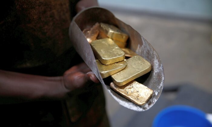 An employee holds gold bars before the refining process at AGR (African Gold Refinery) in Entebbe, Uganda, on Oct. 4, 2018. (Baz Ratner/Reuters)