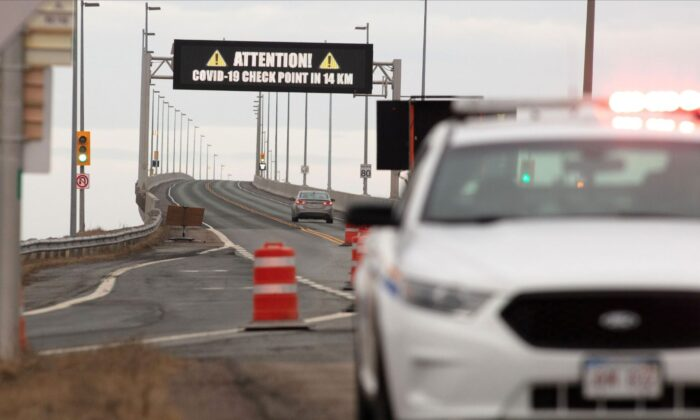 An RCMP vehicle in front of the Confederation Bridge as a vehicle passes under a warning sign of the coronavirus disease (COVID-19) checkpoint on Prince Edward Island at Cape Jourimain, New Brunswick, Canada, on April 2, 2020. (Reuters/John Morris)