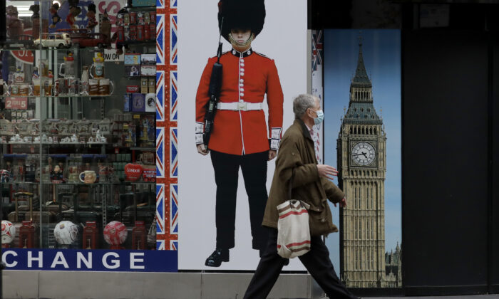 A person wearing a face mask walks past a temporarily closed souvenir store on Oxford Street, during England's second CCP virus lockdown in London, on Nov. 23, 2020. (AP Photo/Matt Dunham)