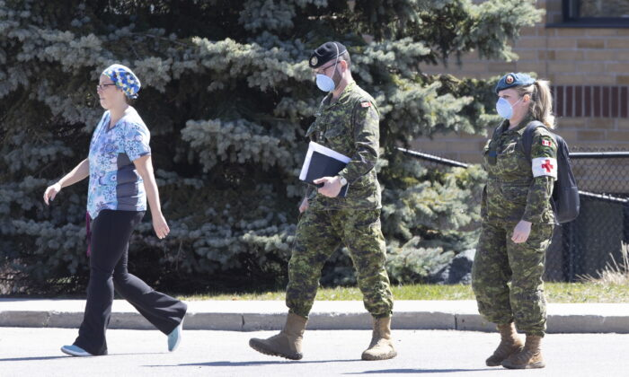 A staff member escorts members of the Canadian Armed Forces in to a long term care home, in Pickering, Ont., on April 25, 2020. (Chris Young/The Canadian Press)