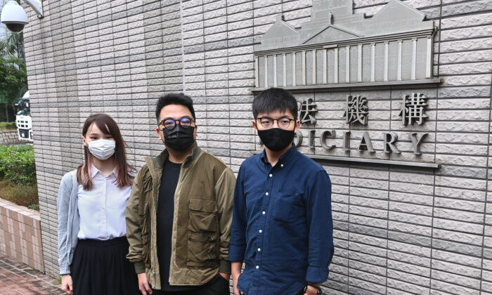 (L-R) Agnes Chow, Ivan Lam, and Joshua Wong pose for pictures before their court session in Hong Kong on Nov. 23, 2020. (Song Bilung/The Epoch Times)