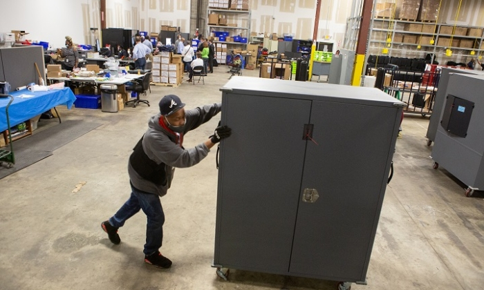 A Fulton County employee moves voting machine transporters to be stored at the the Fulton County Election Preparation Center in Atlanta, Ga., on Nov. 4, 2020. (Jessica McGowan/Getty Images)