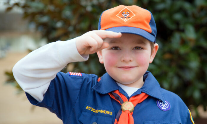 A Cub Scout gives the Boy Scout salute. (Rob Hainer/Shutterstock)