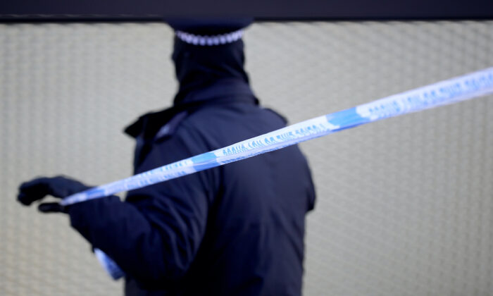 In this file image a policeman sets up tape at a crime scene in London. (Christopher Furlong/Getty Images)