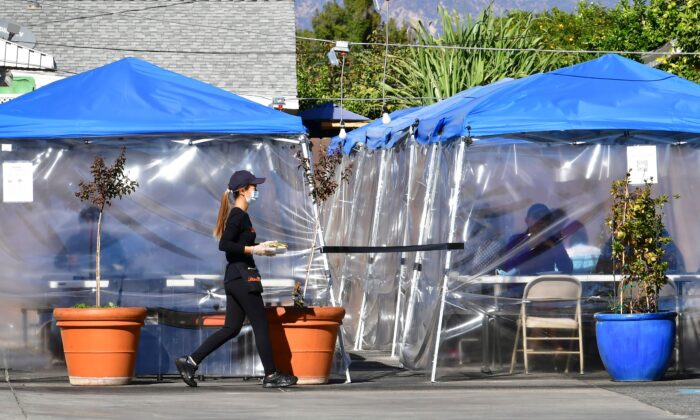 A waitress delivers orders to diners seated outdoors under tents in a restaurant's parking lot in Alhambra, Calif., on Nov. 17, 2020. (Frederic J. Brown/AFP via Getty Images)