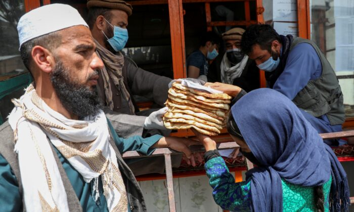 An Afghan girl receives free bread distributed by the government, outside a bakery, during the CCP virus disease (COVID-19) outbreak in Kabul, Afghanistan, on May 3, 2020. (Omar Sobhani/Reuters)